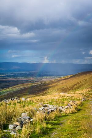 co kerry: Sunshine and raining down with rainbow on the countryside in Kerry in Ireland