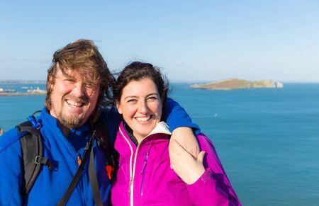 mujer enamorada: moda joven que sonríe y que abrazan en Irlanda en Howth con el mar irlandés en el fondo