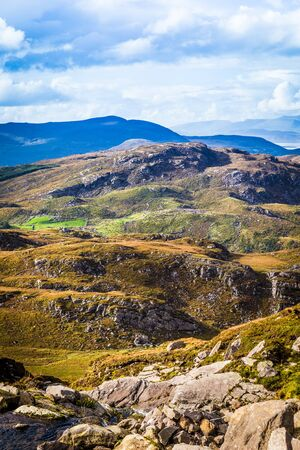 co  kerry: Undulating green, purple and yellow rocky landscape in Kerry in Ireland Stock Photo