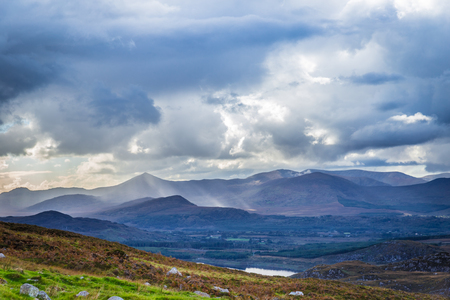 co  kerry: Sun rays piercing through the storm clouds touching the Irish landscape on a dark day in Ireland
