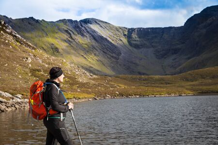 devonian: Female hiker with trekking poles and backpack looking towards the Macgillycuddys Reeks  mountain range in the background