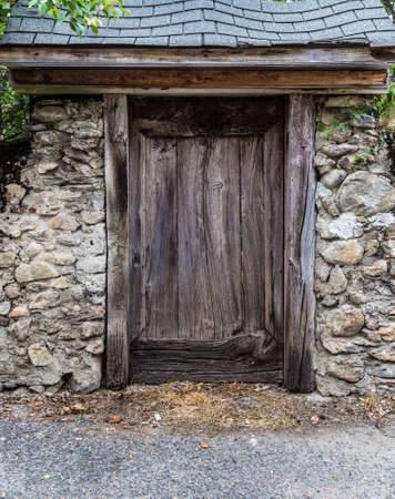 view of a wooden doorway: Old worn rustic strong looking wooden door in a small shed