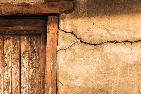 view of a wooden doorway: Cracked lime stone wall and detail of an old wooden door Stock Photo