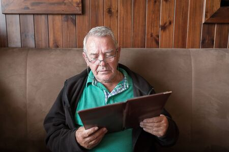 sober: Sober senior man smiling and reading a restaurant menu ready to order food Stock Photo