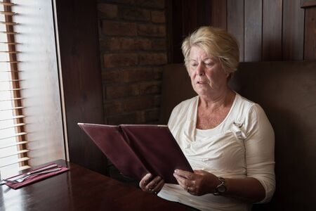sober: Sober senior woman reading a restaurant menu ready to order food