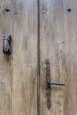 view of a wooden doorway: Detail of an old worn rustic wooden door with termite holes typical for Southern France in Foix in France