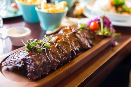 Baby back ribs with sauce served on a wooden plate with side dishes and sauces Stock Photo