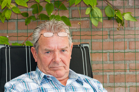 grouchy: Grumpy old man sitting outside in his garden with reading glasses on his forehead Stock Photo