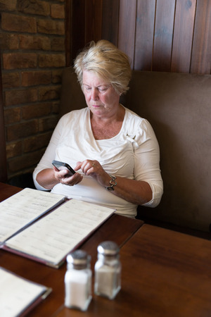 restrained: Restrained senior woman sitting in a restaurant reading messages on her smartphone Stock Photo