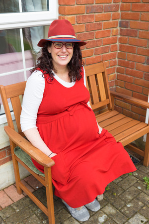 loose fitting: Pregnant lady with glasses wearing a red dress and hat with a big smile sitting in front of her house on a wooden bench