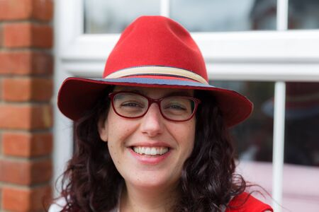 loose hair: Head shot of a young woman with glasses wearing a red dress and hat with a big smile sitting in front of her house