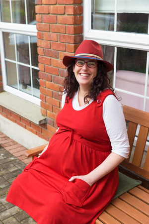 loose fitting: Pregnant woman with glasses wearing a red dress and hat with a big smile sitting in front of her house on a wooden bench