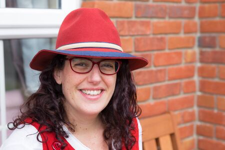 loose fitting: Head shot of a woman with glasses wearing a red dress and hat with a big smile sitting in front of her house