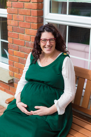 Pregnant woman with glasses wearing a green maternity dress and holding her pregnant belly with a big smile sitting in front of her house on a wooden bench Stock fotó