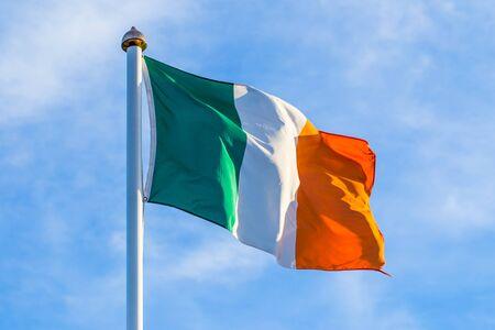 Bandera irlandesa ondeando en el viento en la madrugada al amanecer contra un cielo nublado azul