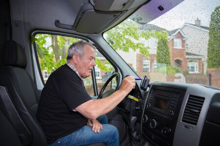 Independent senior in retirement setting up satellite navigation in his transport van 写真素材