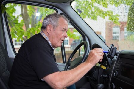 Independent retired senior working as courier setting satellite navigation in his transport van 写真素材