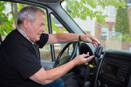 Independent senior in retirement working as courier setting satellite navigation in his transport van