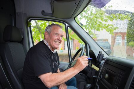 Smiling senior in retirement working as courier setting satellite navigation in his transport van 写真素材