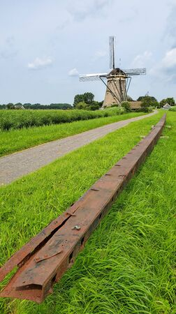 Large windmill sail axle with a windmill in the background in the Netherlands countryside