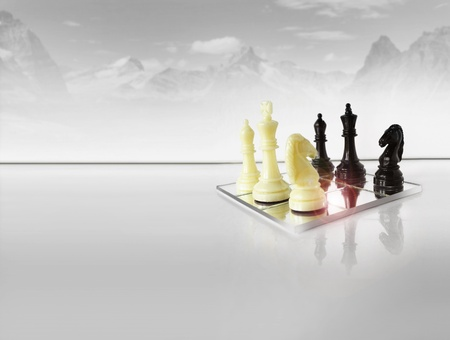 Chess pieces on white reflective foreground with abstract winter mountain scape in background photo