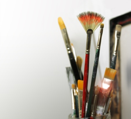 A group of artist paint brushes in modern white studio space Stock Photo