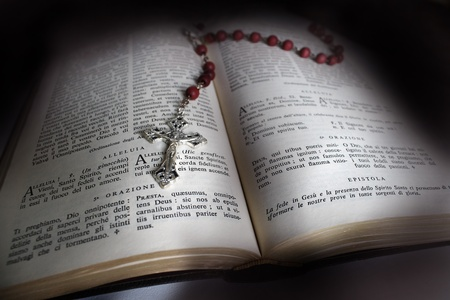 Holy Bible open with a red rosary on top photo