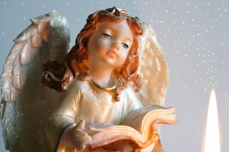 Christmas Angel reading a book with candle flame photo