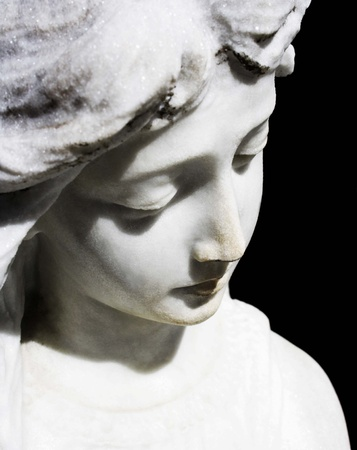 the detail: Detail of a face of an Angel sculpture in the black background Stock Photo