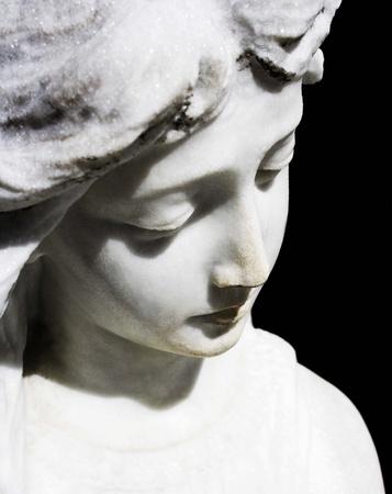 christian angel: Detalle de una cara de una escultura de Angel en el fondo negro Foto de archivo