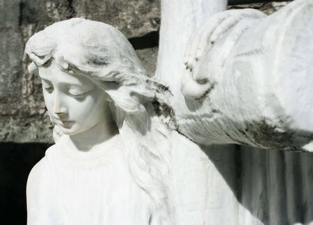 christian angel: Angel sculpture with a Cross behind and a wallstones in the background Stock Photo