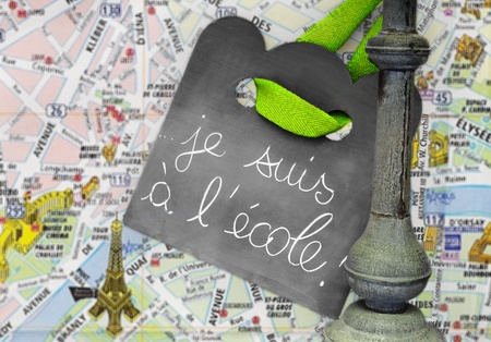 Blackboard hanging on a pole with writing Je suis � l