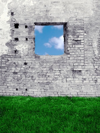 An antique grungy brickwall with grass and an opening in the sky
