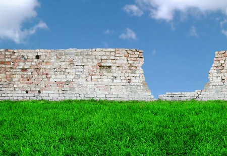 An antique crumbling brickwall with grass and sky Stock Photo