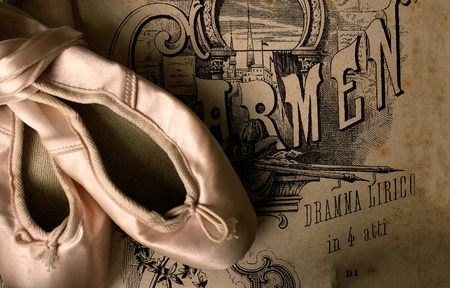 carmen: A pair of ballet slippers with a poster of the opera Carmen in the background Stock Photo