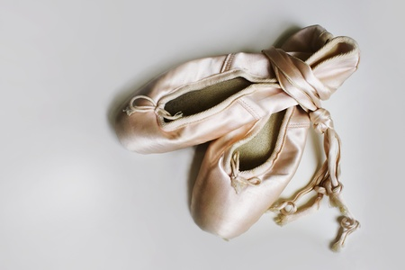 A pair of ballet slippers in light gray background