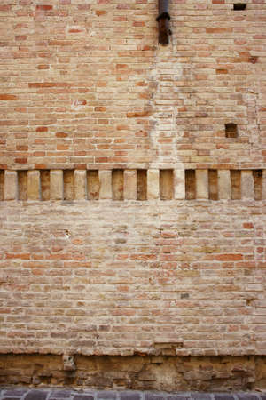 medioeval: Medioeval wall background with a center line of vertical bricks as a decoration and up a part of a gutter