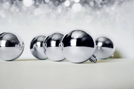 Photo of silver Christmas balls on bright background photo