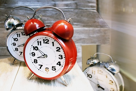Three round shaped alarm clocks, one red and the other two metallic