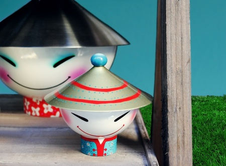 Couple of ceramic figures with metallic hats, sky and grass in the background Stock Photo