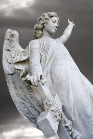 Beautiful sculpture of an angel with a grey sky on the background