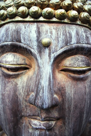 A close up of a beautiful sculpture carved in stone face of Buddha photo