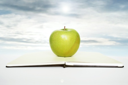 open minded: Open book with a green apple above of it in the beautiful sky on the background