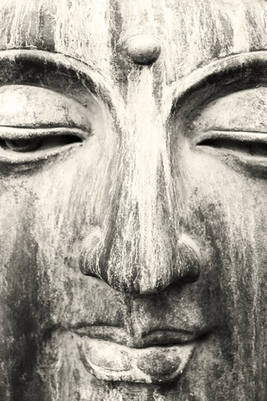 A close up of a beautiful sculpture carved in stone face of Buddha in black and white with a little sepia filter Stock Photo