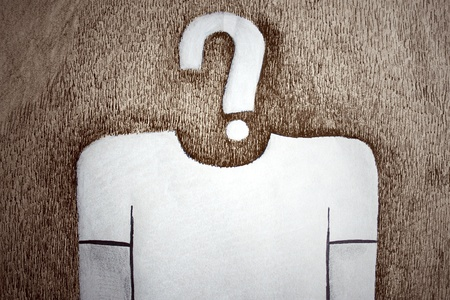 a drawing representing a stylized man with a question mark instead of head on light brown paper Stock Photo