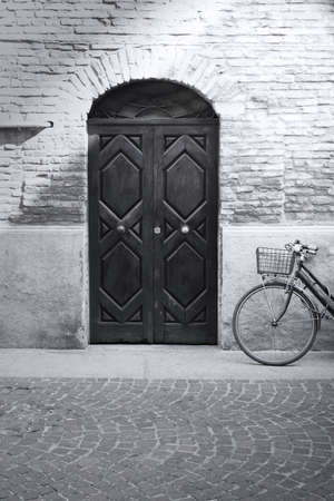 An old fashion detail of a facade of an antique building with a bicycle leaning against the wall in black and white Stock Photo - 12956853