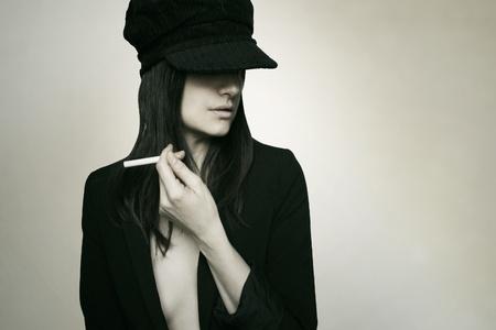彼女の手の間タバコを持つポーズ美しいトレンディな少女