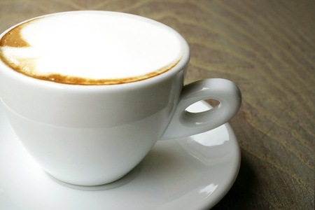 Close up of a cappuccino cup on wooden table Stock Photo - 13694612