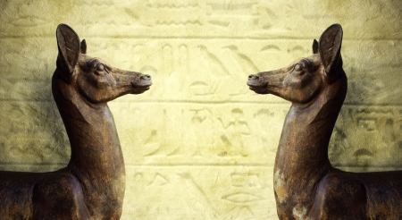 Two wonderful Egyptian statues profile that look each other with hieroglyphic on the background photo