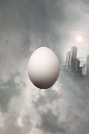 surrealist: Surrealist float of an egg between cloudy dramatic sky with a modern city on the background